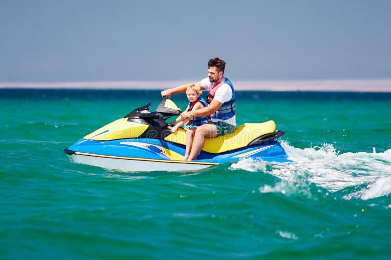 Familia, padre feliz, emocionado e hijo divirtiéndose en el esquí del jet en las vacaciones de verano fotografía de archivo