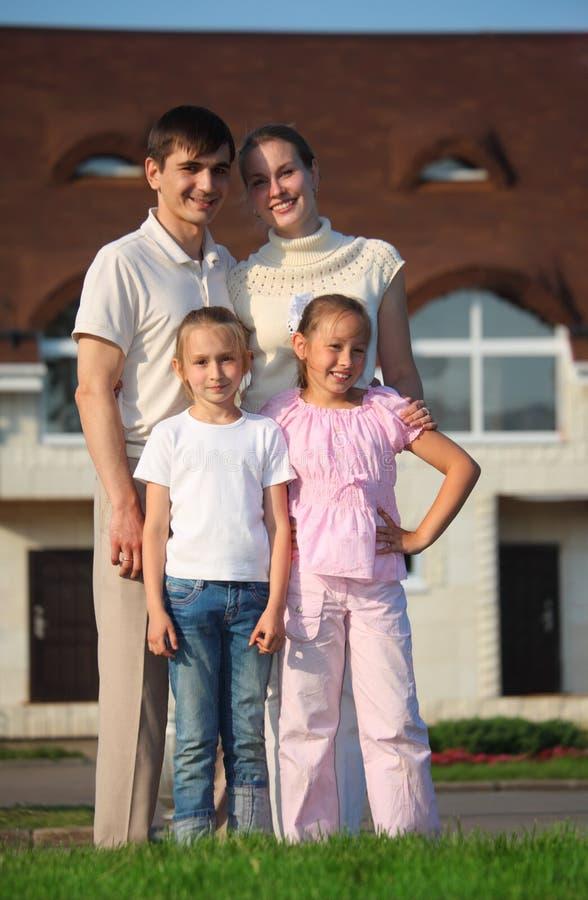 Familia a partir de cuatro soportes en hierba contra casa foto de archivo libre de regalías