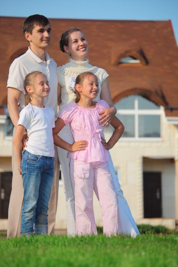 Familia a partir de cuatro soportes en hierba contra casa foto de archivo