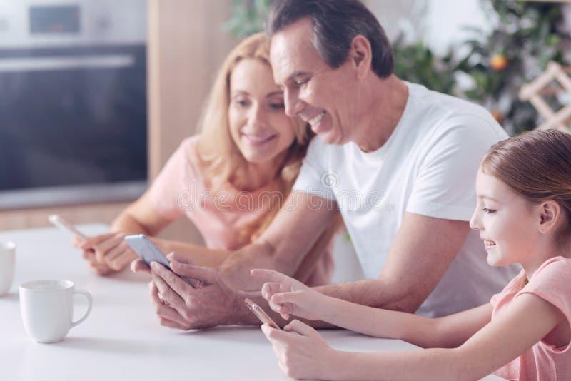 Familia positiva alegre que se sienta junto foto de archivo libre de regalías