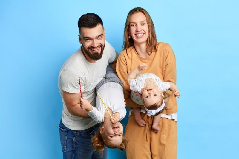 Familia positiva alegre sosteniendo a sus adorables hijos de cabeza fotos de archivo libres de regalías