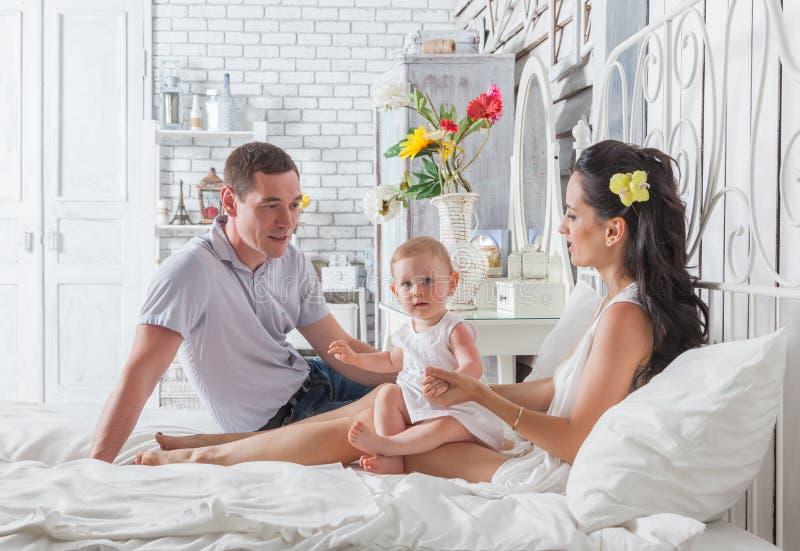 Familia preciosa que se sienta junto en la cama fotos de archivo