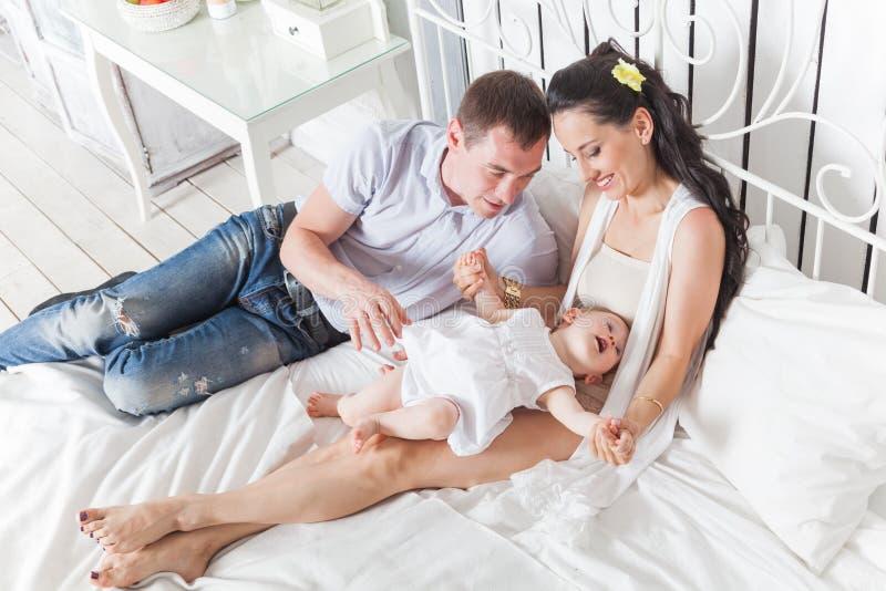 Familia preciosa que se sienta junto en la cama imagen de archivo libre de regalías