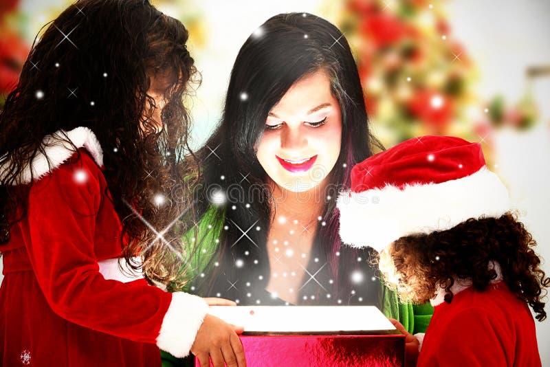 Familia que abre el regalo de Navidad mágico imágenes de archivo libres de regalías