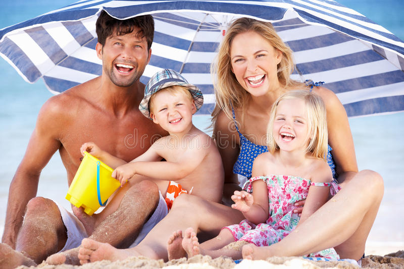 Familia que abriga de Sun bajo el parasol de playa fotografía de archivo