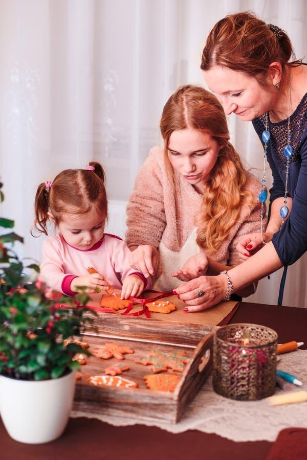 Familia que adorna las galletas cocidas del pan de jengibre de la Navidad fotografía de archivo