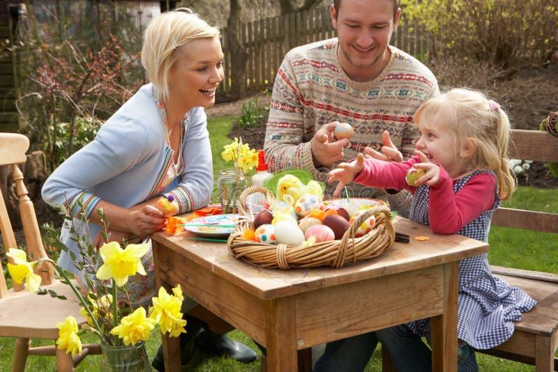 Familia que adorna los huevos de Pascua en el vector al aire libre imagen de archivo