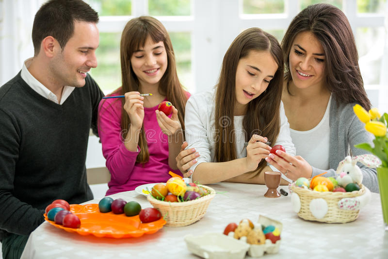 Familia que adorna los huevos de Pascua juntos imagen de archivo