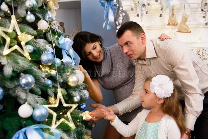 Familia que adorna un árbol de navidad Hombre joven con su hija que le ayuda a adornar el árbol de navidad fotografía de archivo