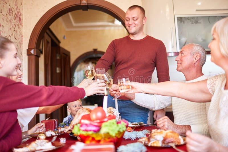 Familia que anima y que bebe en acción de gracias en un fondo borroso Día de fiesta de la familia que recolecta concepto foto de archivo