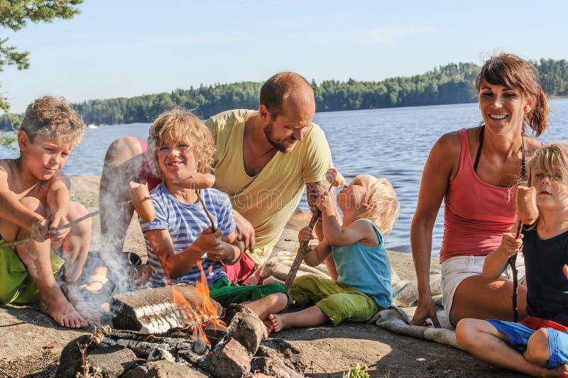 Familia que asa a la parrilla las salchichas en la hoguera foto de archivo