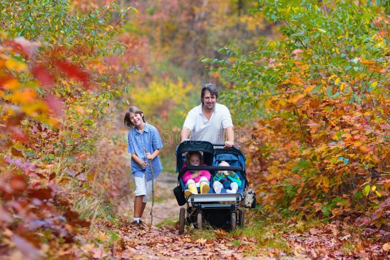 Familia que camina con el cochecito en parque del otoño imagen de archivo
