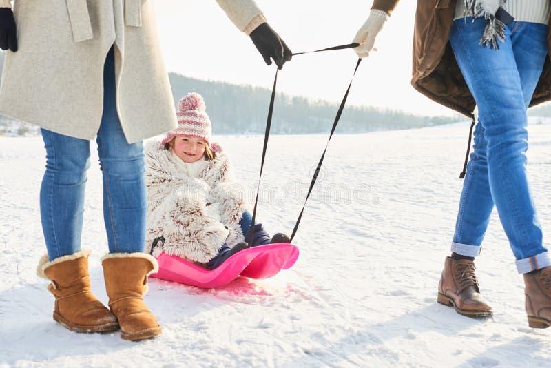 Familia que camina con el niño en el trineo fotos de archivo