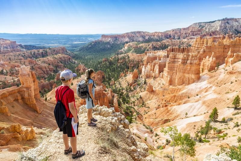 Familia que camina en Bryce Canyon National Park, Utah, los E.E.U.U. que consideran hacia fuera una visión escénica imagen de archivo libre de regalías