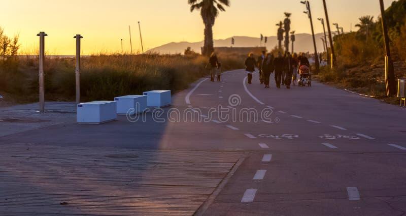 Familia que camina en un lugar hermoso en la puesta del sol imagenes de archivo