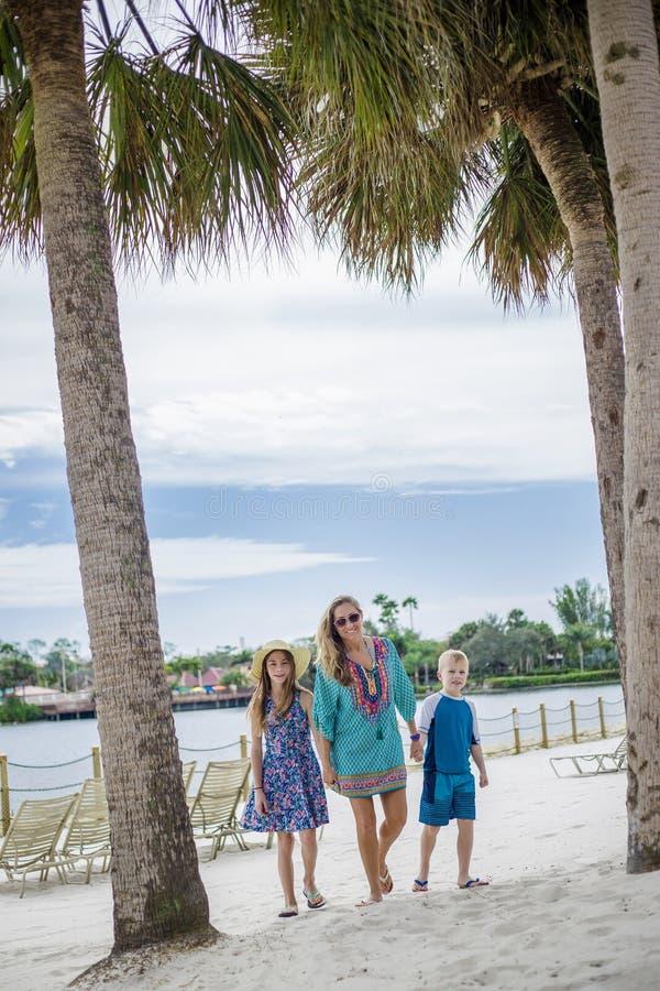 Familia que camina junto en una playa en un complejo playero tropical imagen de archivo libre de regalías
