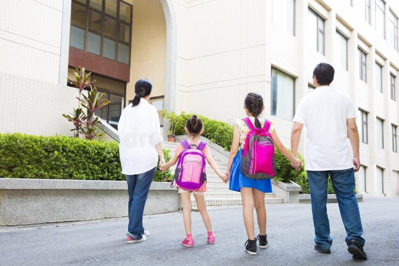Familia que camina a la escuela con los niños foto de archivo