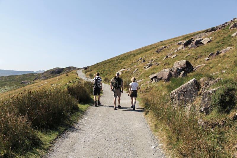 Familia que camina a lo largo del rastro a Snowdon, País de Gales imagenes de archivo