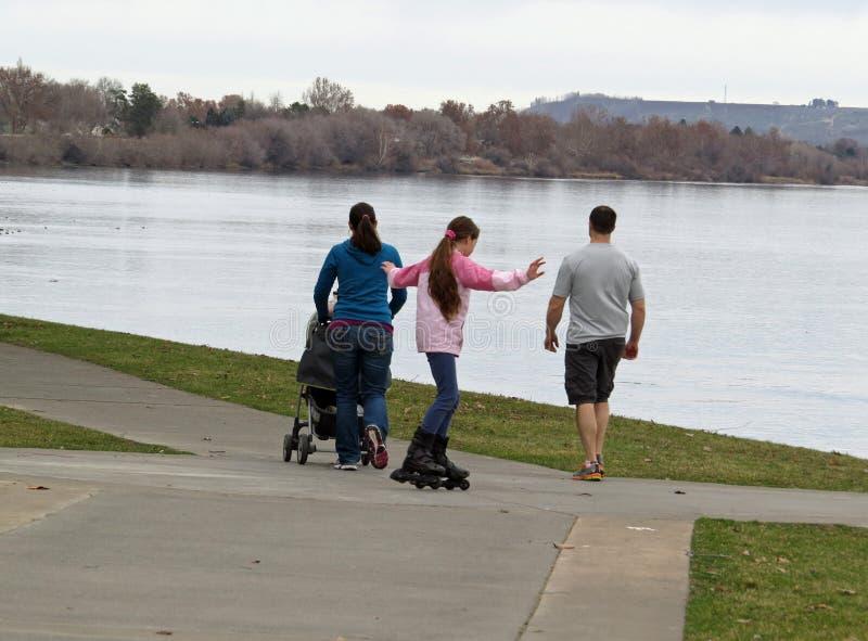 Familia que camina por el río imagenes de archivo