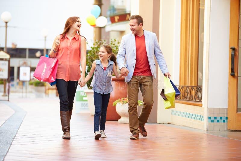 Familia que camina a través de alameda con los panieres fotos de archivo