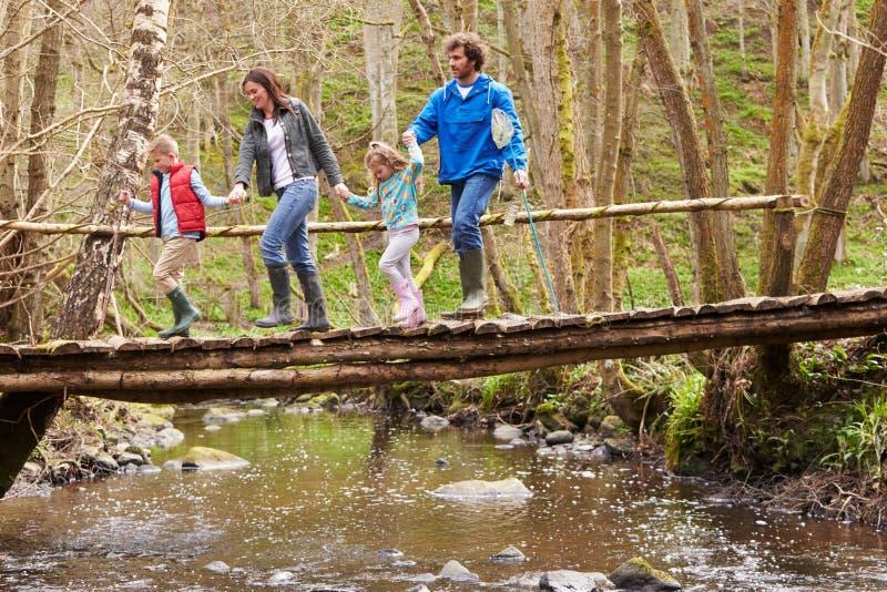 Familia que camina a través del puente de madera sobre corriente en bosque imagen de archivo