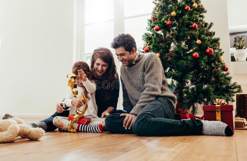Familia que celebra la Navidad en casa con las porciones de regalos fotos de archivo