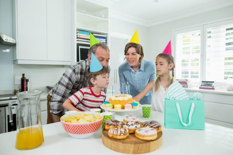 Familia que celebra su cumpleaños de los hijos en cocina imagen de archivo