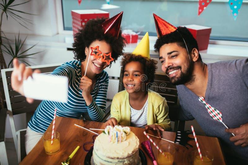 Familia que celebra un cumplea?os junto en casa para hacer el selfie fotografía de archivo
