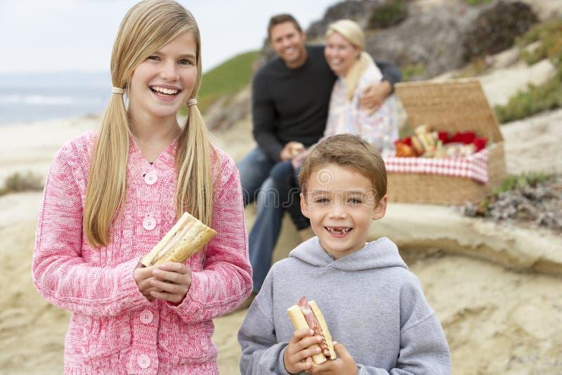 Familia que cena el fresco del Al en la playa imagenes de archivo