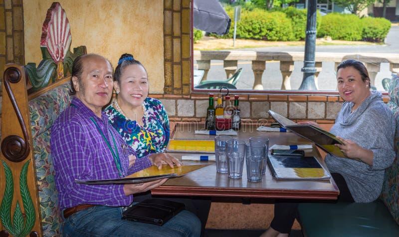 Familia que cena hacia fuera foto de archivo