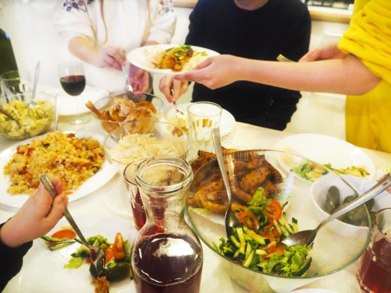 Familia que cena junto que se sienta en la tabla de madera imagenes de archivo