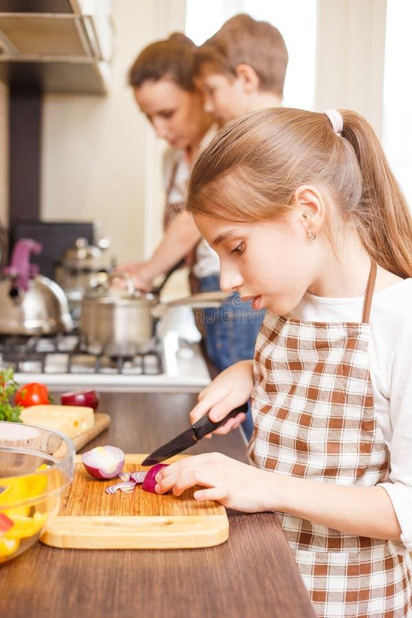 Familia que cocina el fondo Cebolla adolescente del corte de la muchacha fotografía de archivo libre de regalías