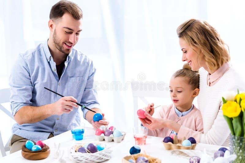 Familia que colorea los huevos de Pascua fotos de archivo
