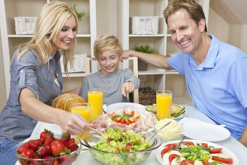 Familia que come el alimento y la ensalada sanos en el vector de cena imagenes de archivo