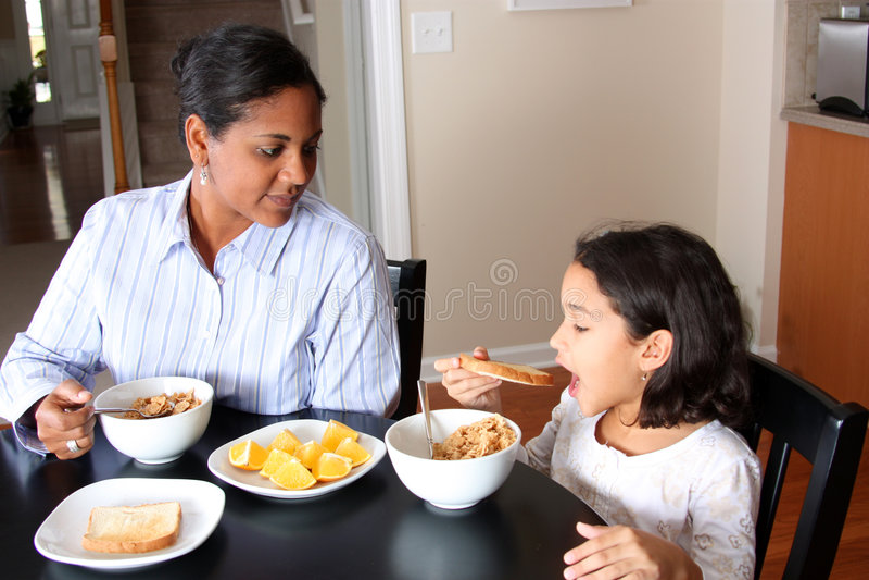 Familia que come el desayuno foto de archivo