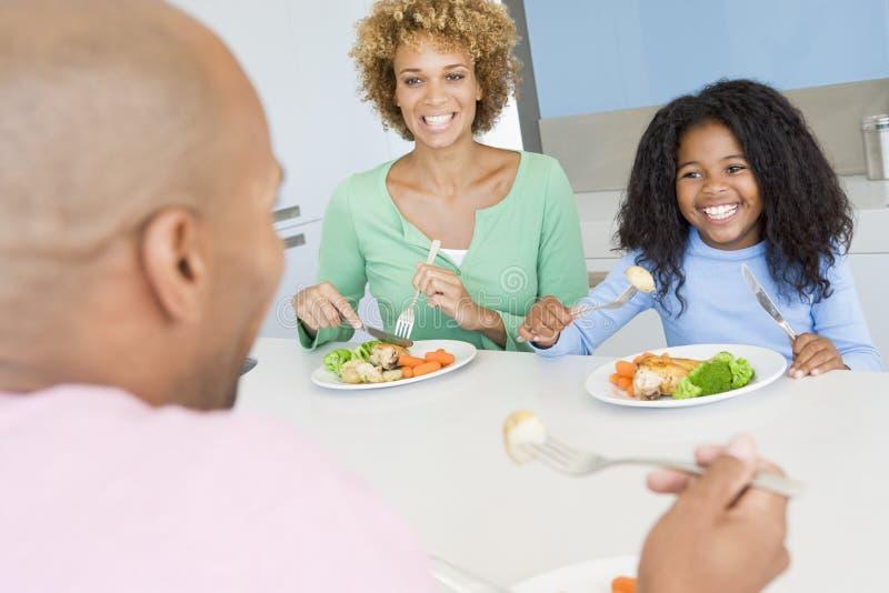 Familia que come la comida de A, mealtime junto imagen de archivo libre de regalías