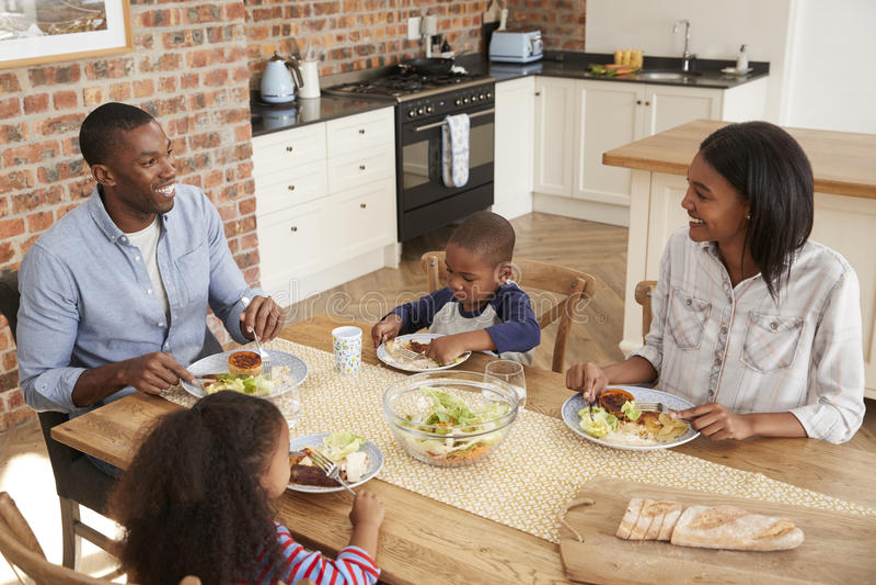 Familia que come la comida en cocina abierta del plan junto imagen de archivo libre de regalías