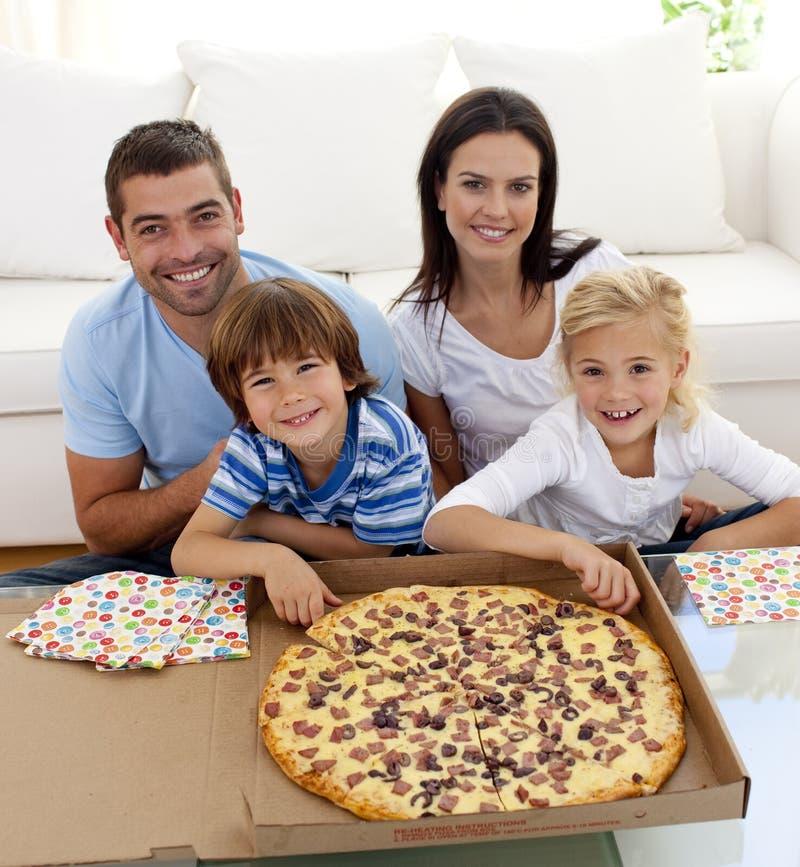 Familia que come la pizza en el sofá fotos de archivo libres de regalías