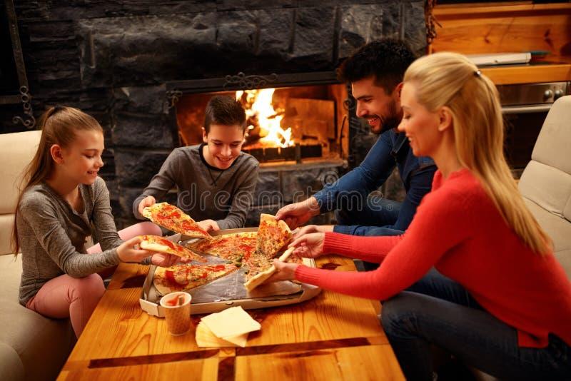 Familia que come la pizza junta para la cena fotografía de archivo libre de regalías