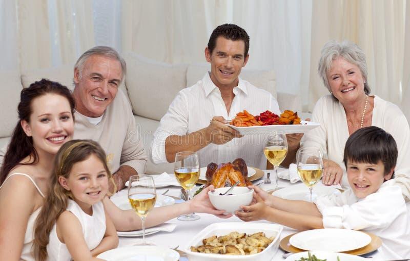 Familia que come para la cena de la Navidad