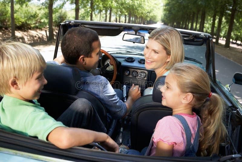 Familia que conduce adelante en un coche de deportes imagen de archivo libre de regalías