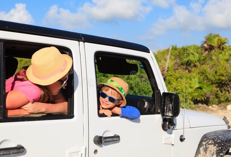 Familia que conduce el coche campo a través en la playa tropical fotos de archivo
