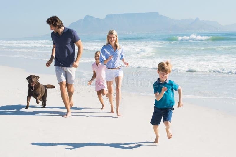 Familia que corre con el perro fotos de archivo libres de regalías