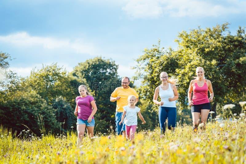 Familia que corre en un prado para el deporte fotografía de archivo