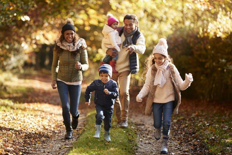 Familia que corre a lo largo de la trayectoria a través de Autumn Countryside fotos de archivo