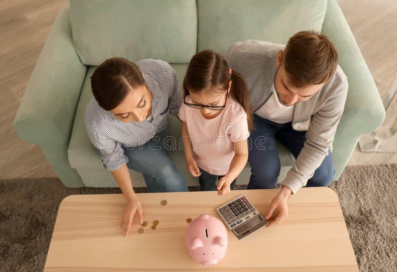 Familia que cuenta el dinero dentro Concepto de los ahorros del dinero fotografía de archivo