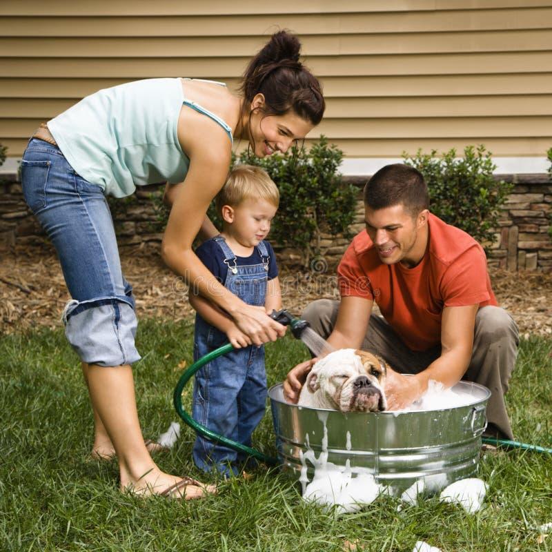 Familia que da a perro un baño.