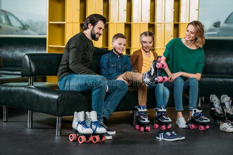 familia que descansa sobre el sofá antes de patinar en pcteres de ruedas imagenes de archivo