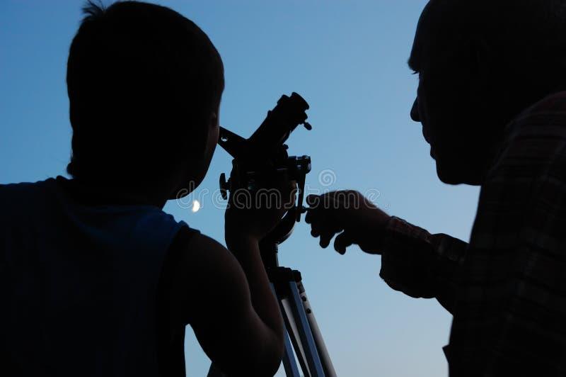 Familia que descubre la luna con un telescopio foto de archivo