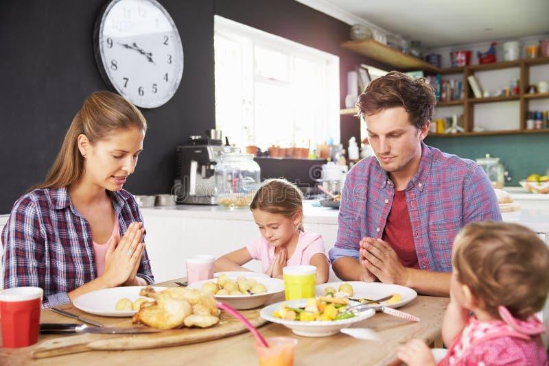 Familia que dice rezo antes de comer la comida en cocina junto fotos de archivo